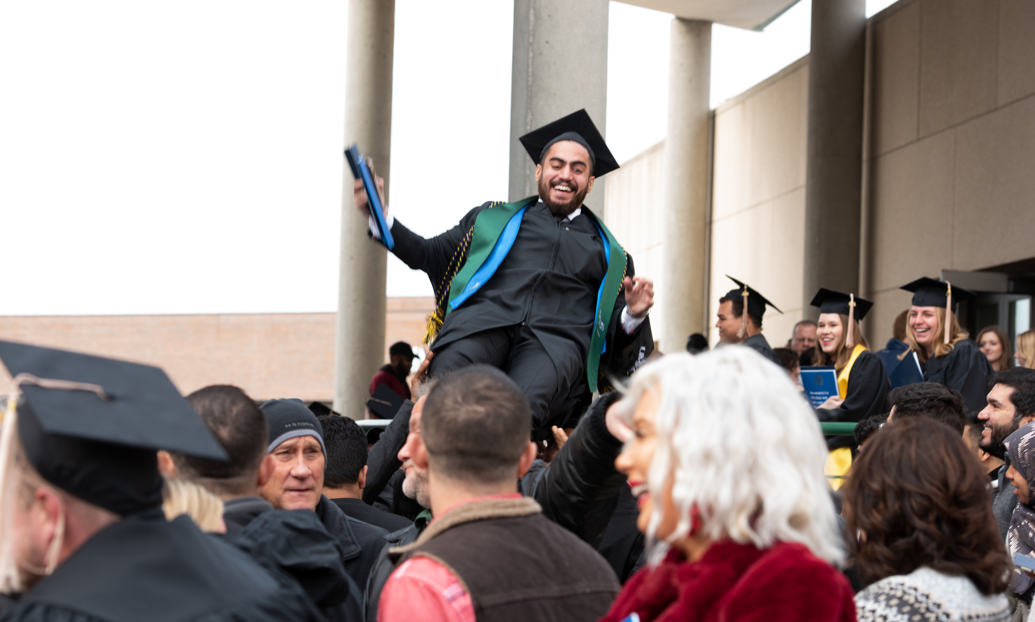 student is lifted onto the shoulders of congratulating friends and family after graduation